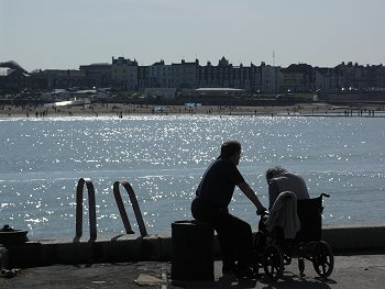 Elderly wheelchair user and carer at the seaside