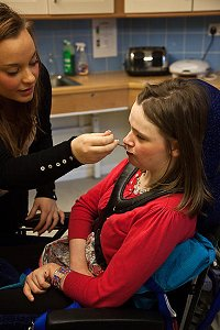 Disabled girl being fed