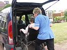 Carer helping disabled person onto minibus
