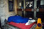 homeless man sleeping in doorway