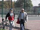 elderly man with bicycle and friend walk past tennis court