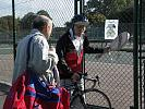 Elderly man and his friend go into tennis courts