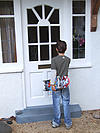 rear view of child with skateboard at front door
