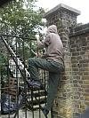 Hooded youth climbing over railings