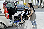 Disabled man helped into adapted car