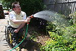 Disabled man in the garden watering plants