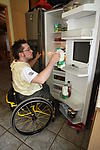 Disabled man opening the fridge, getting the milk