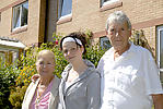 Elderly couple with granddaughter in grounds of sheltered housing