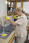 Elderly lady washing up in her kitchen
