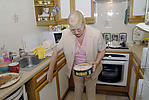 Elderly lady preparing food in her kitchen in a sheltered housing flat