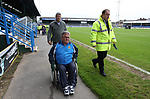 Disabled football supporter and carer escorted to seating area