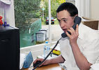 Man with Down's Syndrome answering telephone at work