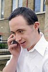 Man with Down's Syndrome happily talking on mobile phone