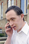 Man with Down's Syndrome talking on mobile phone