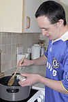 In the community: Man with learning disability preparing a meal