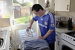 Man with Down's Syndrome ironing at home