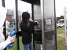 Teenage girl hoodie vandalising phone box