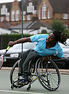 Disabled sports person powers a tennis shot