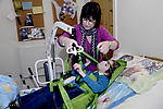 Carer helping disabled boy into hoist
