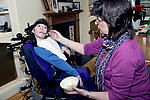 Carer feeding young disabled person