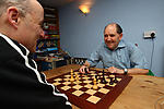 Elderly man and carer play chess in community centre