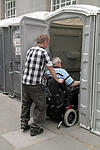 Disabled person with helper using outside toilet
