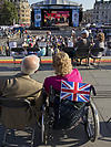 Disabled couple watching the London 2012 Paralympics on a big screen in Trafalgar Square