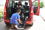 Carer securing wheelchair in adapted car