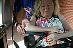 Carer helping diabled woman in adapted car