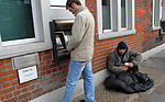 Beggar next to man using cash machine